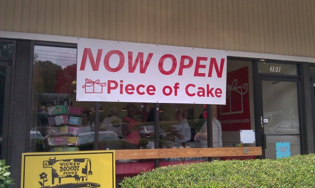 A temporary sign hangs at the new location of Piece of Cake in Vinings.