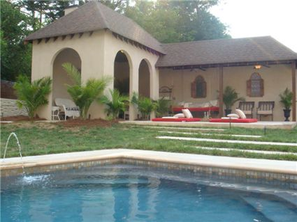 An exquisite setting for a swimming pool and adjacent pool house/cabana.