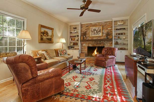 A light-filled living room is anchored by a cozy fireplace in this Vinings home for sale. Click on the image for more photos and information.