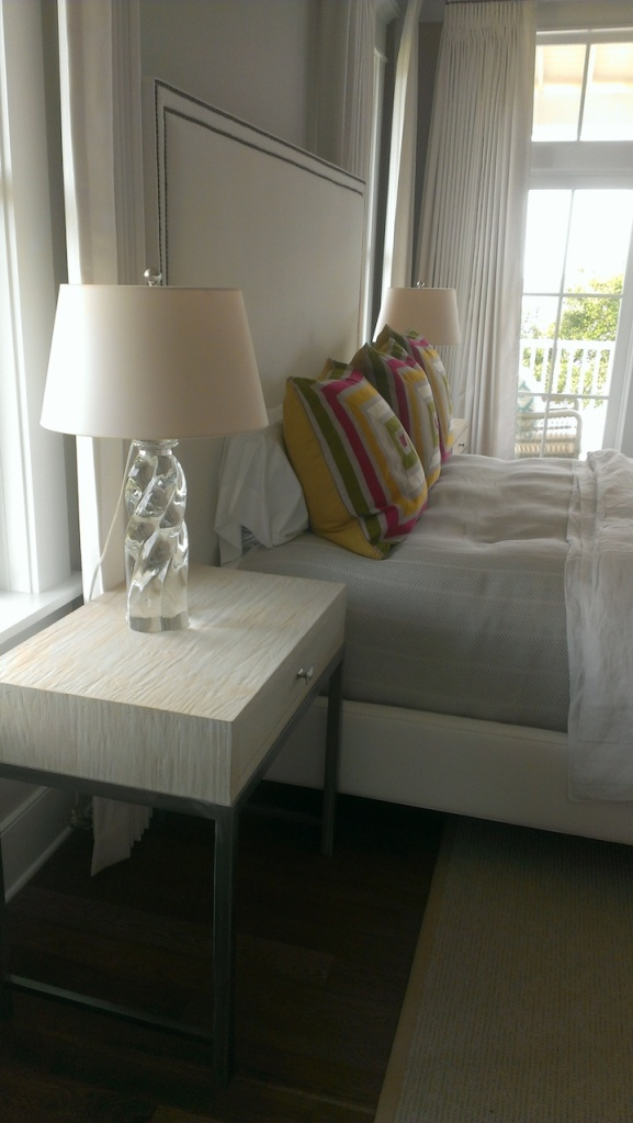 In master bedroom,  theere is a white focus with splashes of bright colors.  Views of the Charleston bay out the window.  Love the lamp!  Available at Circa Lighting.