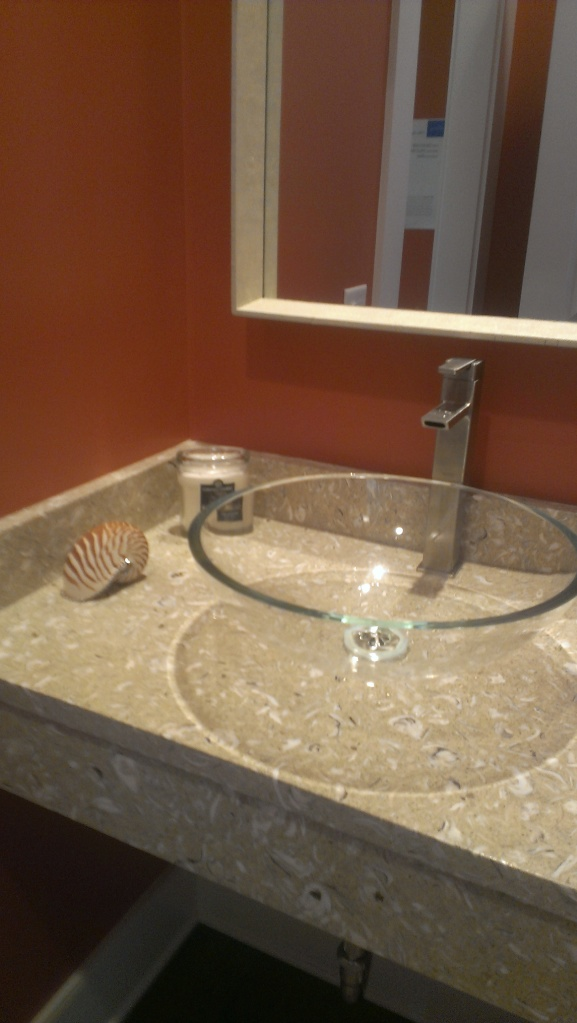 Powder room on main.  Love the fossil or shell material, not sure if its stone or fabricated?